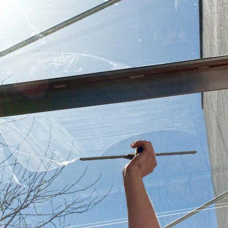 Fensterputzer Neumarkt bei der Reinigung einer Glasüberdachung über der Eingangstür.